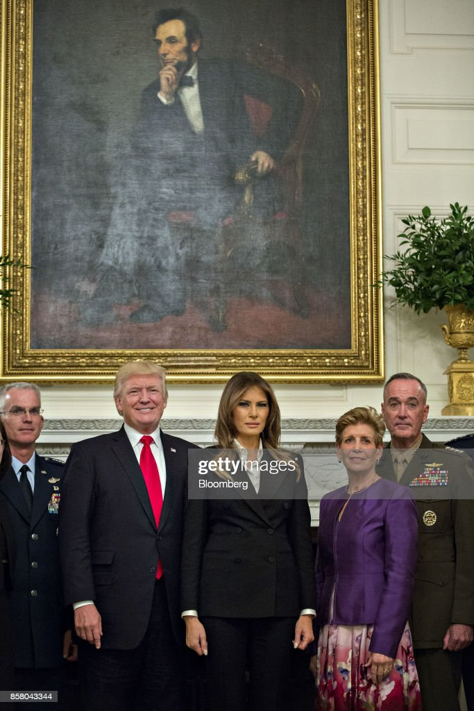 U.S. President Donald Trump, center left, and U.S. First Lady Melania Trump, center right, stand for an official photograph with senior military leaders and spouses including General Joseph Dunford, chairman of the Joint Chiefs of Staff, right, and General Paul Selva, vice chairman of the Joint Chiefs of Staff, left, in the State Dining room of the White House in Washington, D.C., U.S., on Thursday, Oct. 5, 2017. President Trump and the First Lady are hosting the group for dinner in the Blue Room of the White House. Photographer: Andrew Harrer/Bloomberg via Getty Images
