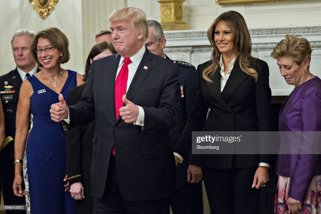 U.S. President Donald Trump, center left, gives a thumbs up next to U.S. First Lady Melania Trump, center right, during an official photograph with senior military leaders and spouses in the State Dining room of the White House in Washington, D.C., U.S., on Thursday, Oct. 5, 2017. President Trump and the First Lady are hosting the group for dinner in the Blue Room of the White House. Photographer: Andrew Harrer/Bloomberg via Getty Images