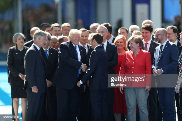 US President Donald Trump center left shakes hands with Emmanuel Macron France's president as other world leaders look on during a summit of world...