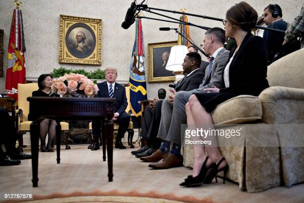US President Donald Trump center left speaks while meeting with workers benefiting from tax reform legislation in the Oval Office of the White House...