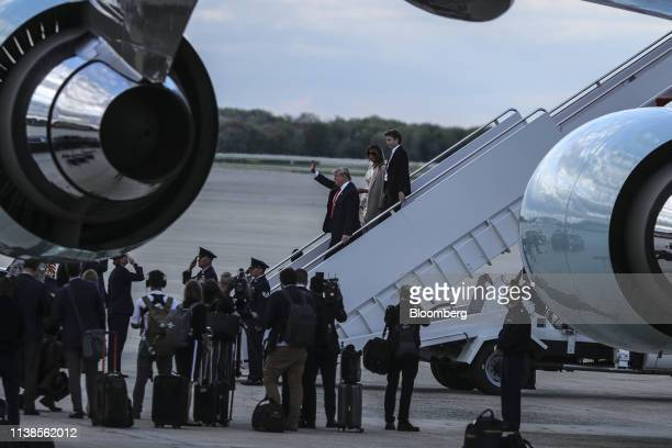 US President Donald Trump center left waves as he walks with US First Lady Melania Trump and son Barron Trump as he arrives aboard Air Force One in...