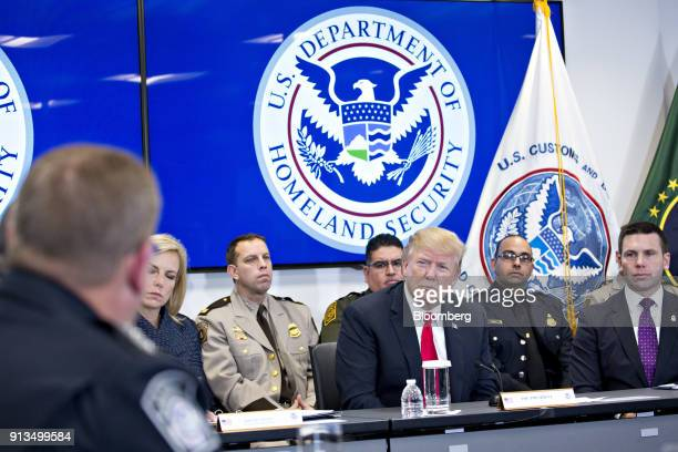 US President Donald Trump center listens during a Customs and Border Protection roundtable discussion after touring the CBP National Targeting Center...