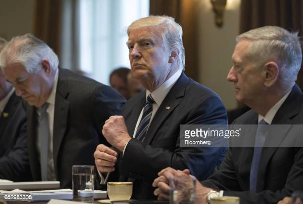 US President Donald Trump center listens during a meeting with members of the Cabinet at the White House in Washington DC US on Monday March 13 2017...