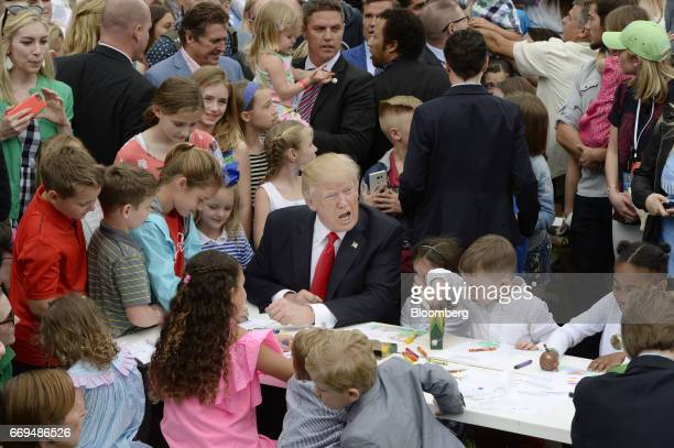 US President Donald Trump center makes cards with children for members of the military during the annual Easter Egg Roll on the South Lawn of the...