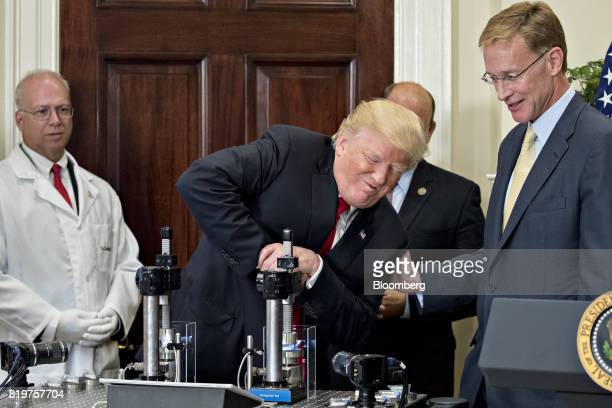 US President Donald Trump center participates in a glass strength test of a Corning Valor vial with Wendell Weeks chairman and chief executive...