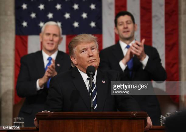 US President Donald Trump center pauses as US Vice President Mike Pence left and US House Speaker Paul Ryan a Republican from Wisconsin applaud...