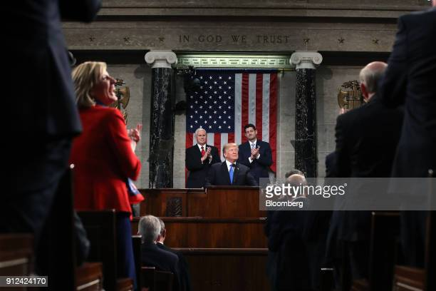 US President Donald Trump center pauses while delivering a State of the Union address to a joint session of Congress at the US Capitol in Washington...