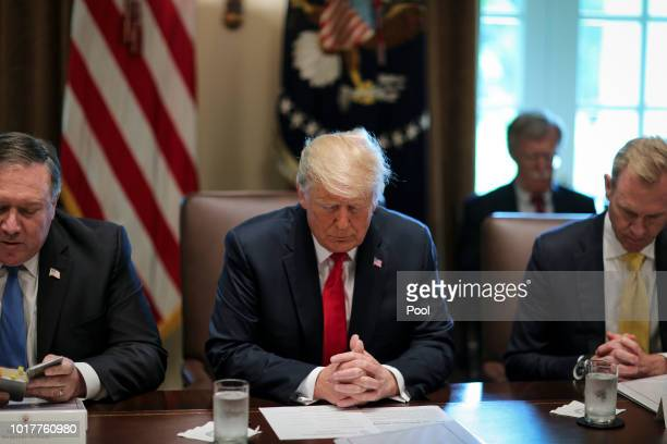 President Donald Trump center prays during a Cabinet Meeting in the Cabinet Room of the White House on August 16 2018 in Washington DC Next to...