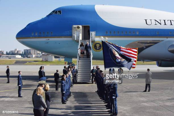 US President Donald Trump center right and US First Lady Melania Trump center left walk down a flight of stairs after stepping out of Air Force One...