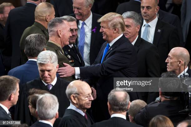 US President Donald Trump center right greets General Joseph Dunford chairman of the Joint Chiefs of Staff center left after delivering a State of...