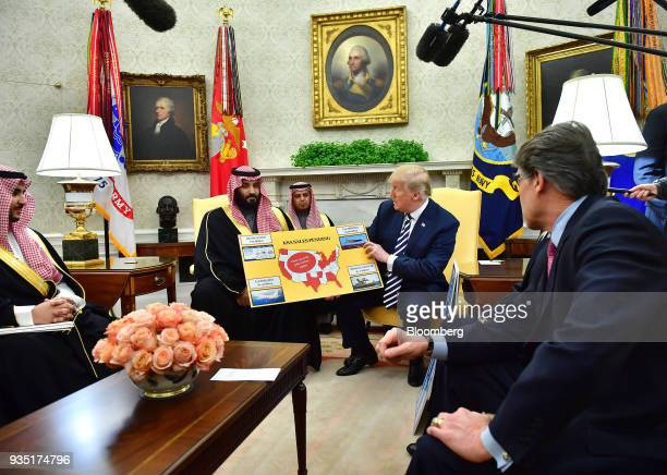 US President Donald Trump center right holds a chart displaying military sales during a meeting with Mohammed bin Salman Saudi Arabia's crown prince...