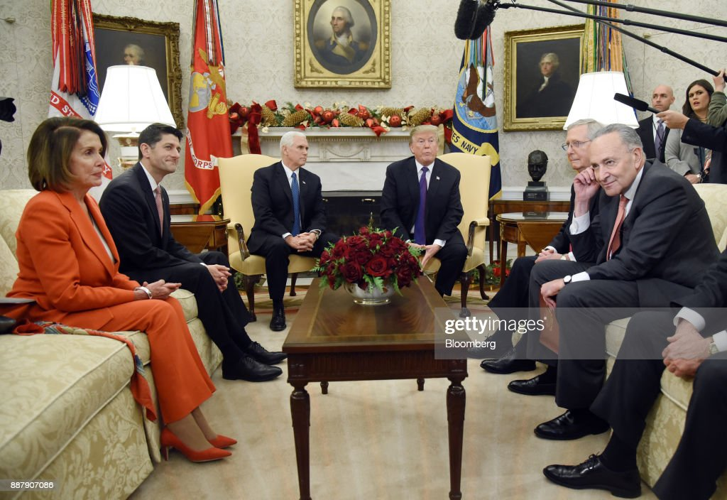 U.S. President Donald Trump, center right, speaks as House Minority Leader Nancy Pelosi, a Democrat from California, from left, U.S. House Speaker Paul Ryan, a Republican from Wisconsin, U.S. Vice President Mike Pence, Senate Majority Leader Mitch McConnell, a Republican from Kentucky, and Senate Minority Leader Chuck Schumer, a Democrat from New York, listen during a meeting in the Oval Office of the White House in Washington, D.C., U.S., on Thursday, Dec. 7, 2017. Trump is meeting with the congressional leaders from both parties to negotiate on a long-term budget deal as Congress prepares to pass a stopgap spending measure to avoid a U.S. government shutdown Saturday. Photographer: Olivier Douliery/Pool via Bloomberg