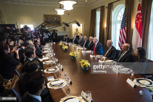 US President Donald Trump center right speaks before a working lunch with Lee Hsien Loong Singapore's prime minister not pictured in the cabinet room...