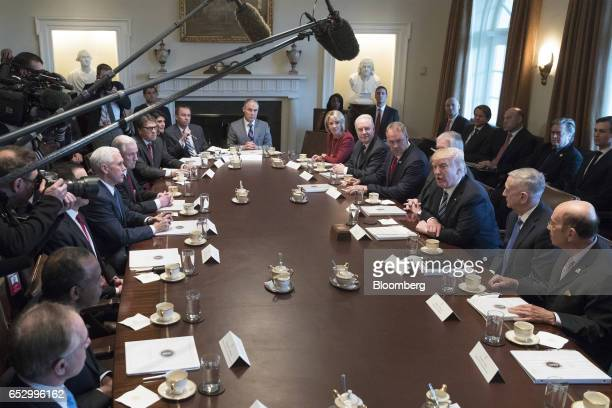 US President Donald Trump center right speaks during a meeting with members of the Cabinet at the White House in Washington DC US on Monday March 13...