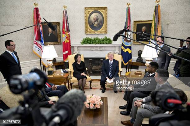 US President Donald Trump center right speaks while meeting with workers benefiting from tax reform legislation in the Oval Office of the White House...
