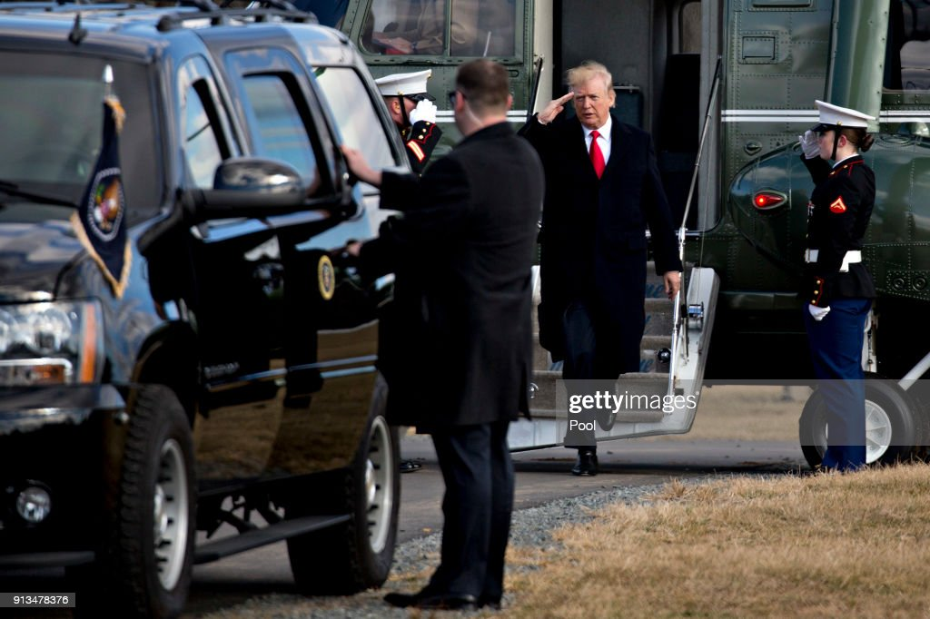 U.S. President Donald Trump, center, salutes while walking off Marine One after landing at Paul Hencken Soccer Fields before visiting the Customs and Border Protection (CBP) National Targeting Center February 2, 2018 in Sterling, Virginia. Trump is looking to ratchet up pressure on lawmakers to consider the immigration proposal he unveiled in TuesdayÕs State of the Union using the visit as an opportunity to again argue his proposal would bolster the countryÕs borders.