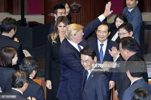 US President Donald Trump center shakes hands and waves as US First Lady Melania Trump center left looks on at the National Assembly in Seoul South...