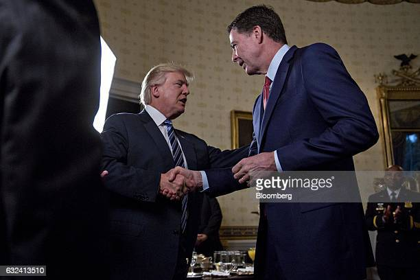 US President Donald Trump center shakes hands with James Comey director of the Federal Bureau of Investigation during an Inaugural Law Enforcement...