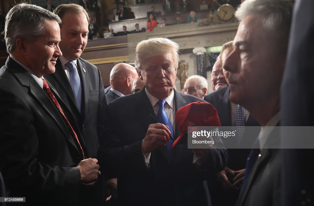 U.S. President Donald Trump, center, signs a hat after delivering a State of the Union address to a joint session of Congress at the U.S. Capitol in Washington, D.C., U.S., on Tuesday, Jan. 30, 2018. Trump sought to connect his presidency to the nation's prosperity in his first State of the Union address, arguing that the U.S. has arrived at a 'new American moment' of wealth and opportunity. Photographer: Win McNamee/Pool via Bloomberg