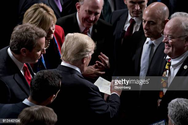 US President Donald Trump center signs his name on letterhead after delivering a State of the Union address to a joint session of Congress at the US...