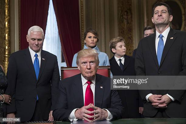US President Donald Trump center sits before formally signing his cabinet nominations into law with Vice President Mike Pence left and US House...