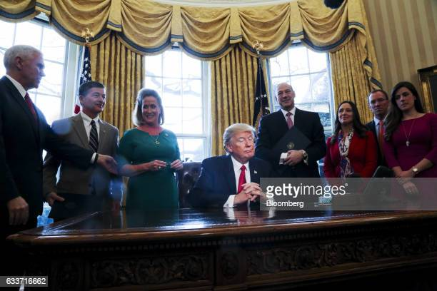 US President Donald Trump center smiles after signing an Executive Order related to the review of the DoddFrank Act in the Oval Office of the White...