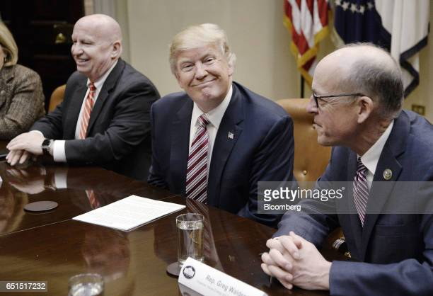 US President Donald Trump center smiles as Representative Greg Walden a Republican from Oregon right and Representative Kevin Brady a Republican from...