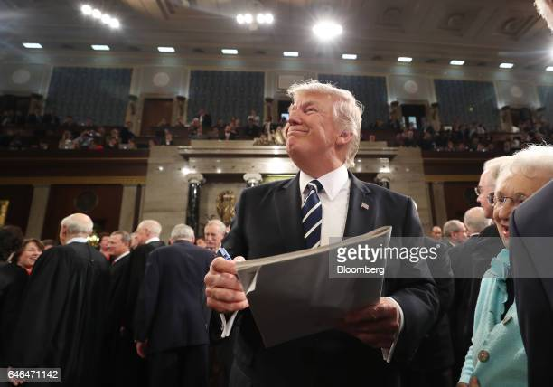 US President Donald Trump center smiles while signing an autograph after a joint session of Congress in Washington DC US on Tuesday Feb 28 2017 Trump...