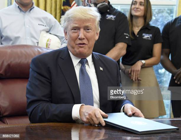 US President Donald Trump center speaks after signing the National Manufacturing Day proclamation in the Oval Office of the White House in Washington...