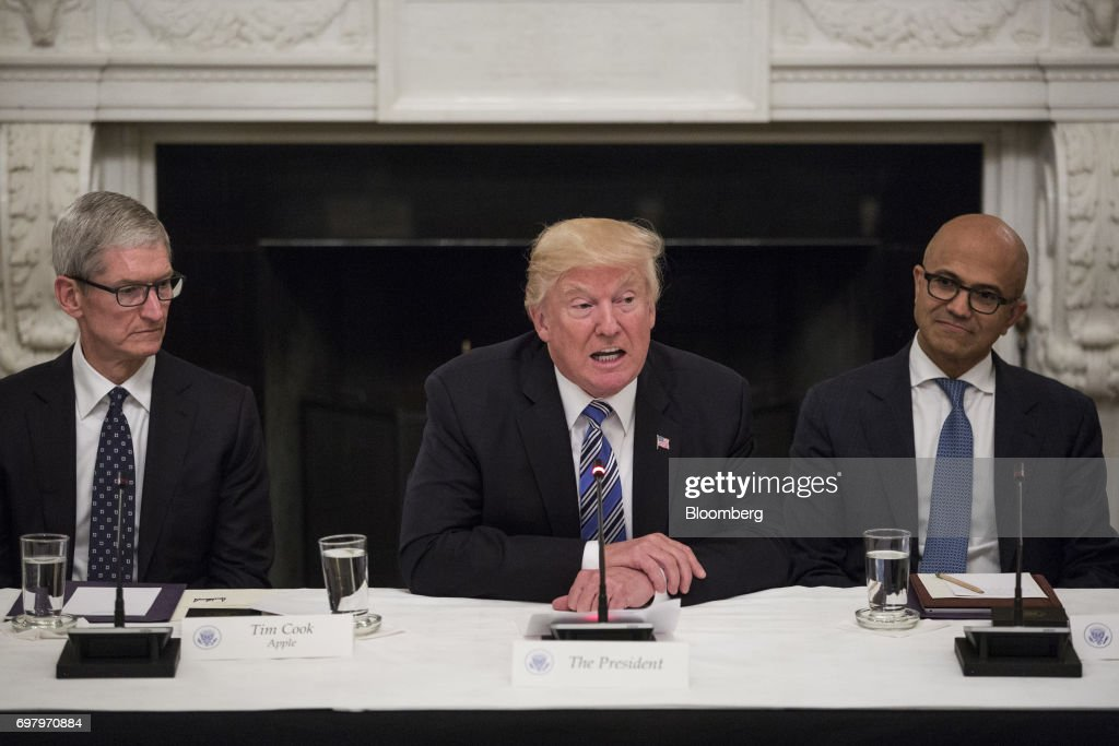 U.S. President Donald Trump, center, speaks as Tim Cook, chief executive officer of Apple Inc., left, and Satya Nadella, chief executive officer of Microsoft Corp., listen during the American Technology Council roundtable hosted at the White House in Washington, D.C., U.S., on Monday, June 19, 2017. Executives from many of the world's largest technology companies gathered for the first meeting of the American Technology Council with Trumpand his senior advisers. Photographer: Zach Gibson/Bloomberg via Getty Images