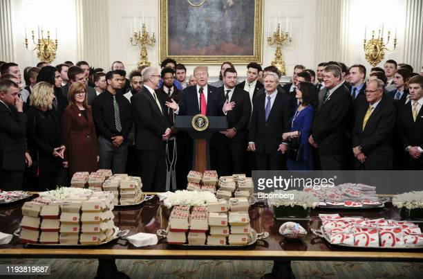 President Donald Trump, center, speaks behind a table of fast food as he welcomes the 2018 Division 1 Football National Champions, the North Dakota...