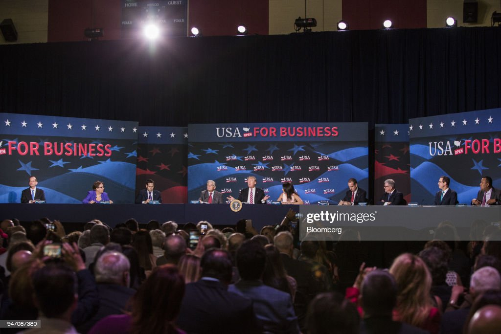 U.S. President Donald Trump, center, speaks during roundtable discussion on tax cuts for Florida small businesses in Hialeah, Florida, U.S., on Monday, April 16, 2018. Trump accused China and Russia of devaluing their currencies, breaking from his own Treasury chief's view that no major trading partners are currency manipulators. Photographer: Scott McIntyre/Bloomberg via Getty Images