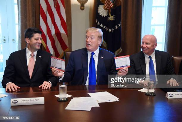 US President Donald Trump center speaks while holding up 'Simple Fair 'Postcard' Tax Filing' cards as US House Speaker Paul Ryan a Republican from...