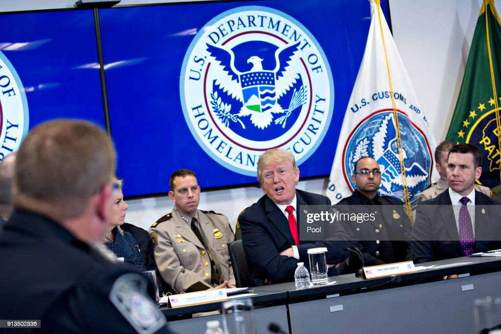 U.S. President Donald Trump, center, speaks while participating in a Customs and Border Protection (CBP) roundtable discussion after touring the CBP National Targeting Center February 2, 2018 in Sterling, Virginia. Trump is looking to ratchet up pressure on lawmakers to consider the immigration proposal he unveiled in Tuesday's State of the Union using the visit as an opportunity to again argue his proposal would bolster the country's borders.