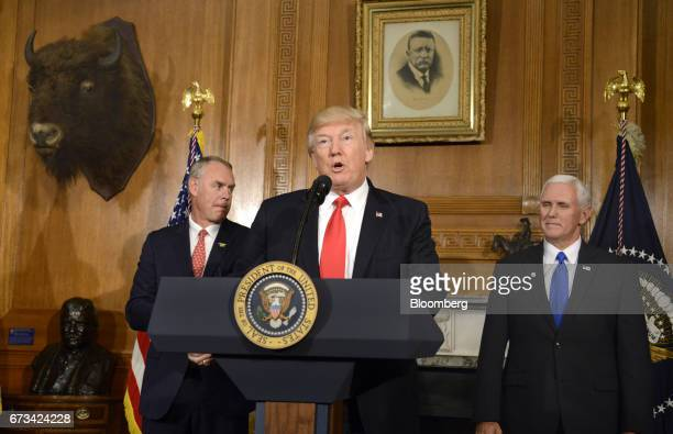 US President Donald Trump center speaks while Ryan Zinke US secretary of interior left and US Vice President Mike Pence before signing an antiquities...