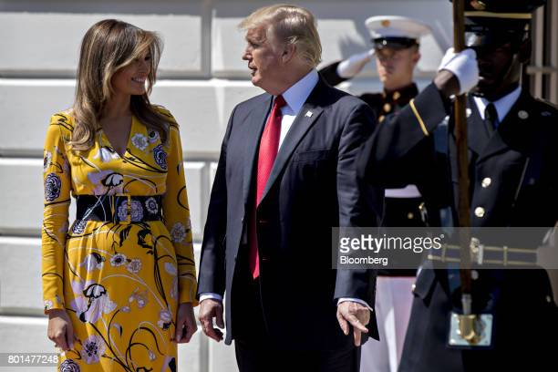 US President Donald Trump center speaks with US First Lady Melania Trump left while walking out of the South Portico of the White House to greet...