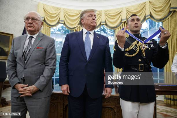 US President Donald Trump center stands before presenting the Presidential Medal of Freedom to Robert Cousy former National Basketball Association...