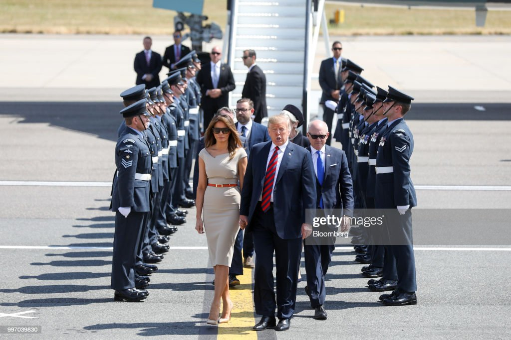 U.S. President Donald Trump, center, U.S. First Lady Melania Trump, left, and Woody Johnson, U.S. ambassador to the United Kingdom, make their way to Marine One after arriving nat London Stansted Airport in Stansted, U.K., on Thursday, July 12, 2018. Trump will avoid London as much as possible as he's whisked off on a tour of prime British real estate to keep him away from protesters during his U.K. visit. Photographer: Chris Ratcliffe/Bloomberg via Getty Images