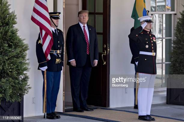 President Donald Trump, center, waits to greet Jair Bolsonaro, Brazil's president, not pictured, at the West Wing of the White House in Washington,...