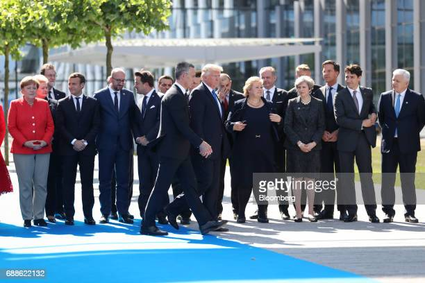 US President Donald Trump center walks with Jens Stoltenberg secretary general of the North Atlantic Treaty Organization as world leaders gather for...