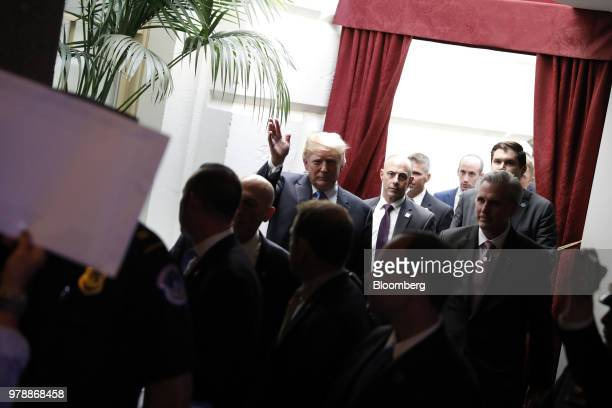 US President Donald Trump center waves as Democratic members of congress demonstrate after a House Republican conference meeting on immigration...