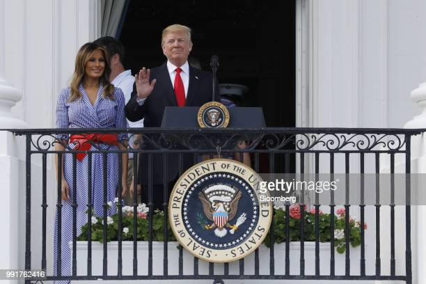 US President Donald Trump center waves as First Lady Melania Trump looks on at a picnic for military families in Washington DC US on Wednesday July 4...