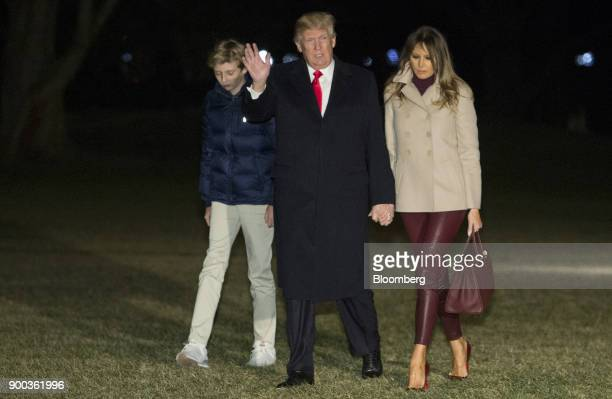 US President Donald Trump center waves as he walks with US First Lady Melania Trump right and son Barron Trump after arriving on Marine One at the...