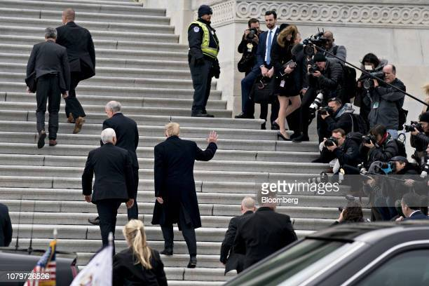 US President Donald Trump center waves to members of the media while arriving to the US Capitol for a meeting with Senate Republicans with US Vice...