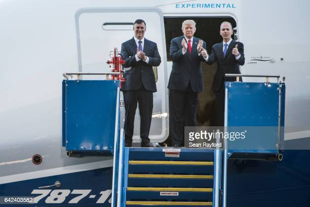 S President Donald Trump center with Boeing representatives Kevin McAllister left and Dennis Muilenburg right exit the Dreamliner 78710 following a...