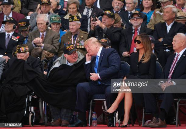 S President Donald Trump chats with an American veteran of The Battle of Normandy as First Lady Melania Trump looks on at the main ceremony to mark...