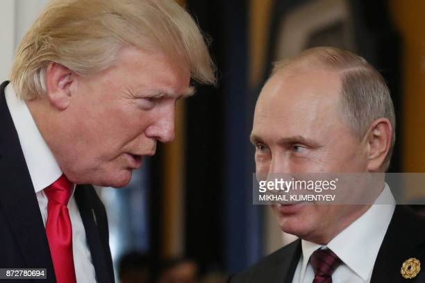 President Donald Trump chats with Russia's President Vladimir Putin as they attend the APEC Economic Leaders' Meeting, part of the Asia-Pacific...