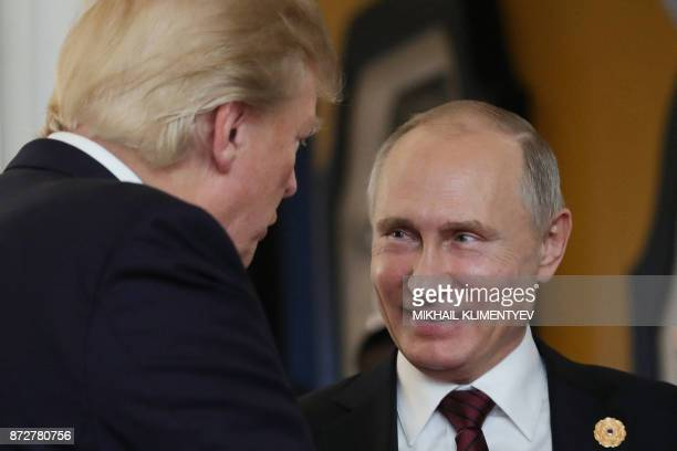 US President Donald Trump chats with Russia's President Vladimir Putin as they attend the APEC Economic Leaders' Meeting part of the AsiaPacific...