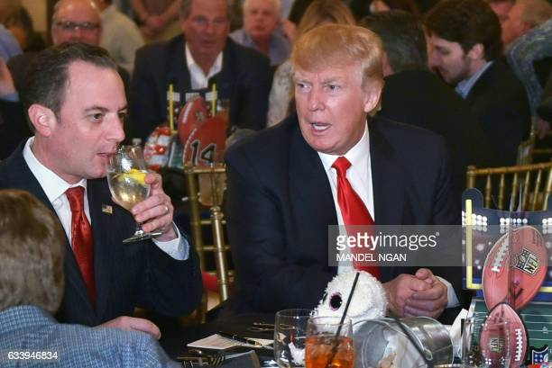 US President Donald Trump chats with White House Chief of Staff Reince Priebus while watching Super Bowl LI at Trump International Golf Club Palm...