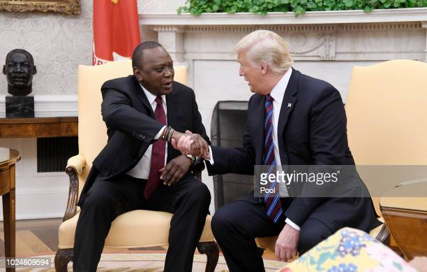 S President Donald Trump checks hands with Kenyan President Uhuru Kenyatta during a bilateral meeting in the Oval Office of the White House August 27...
